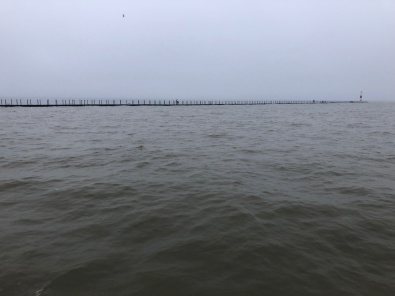 Gray day on the water. In the distance, a pier stretches off to a lighthouse, with a few people braving the weather.
