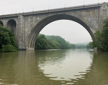 The arch of a stone bridge over a river reflects in the water to make a circle