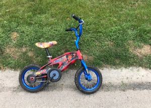 A child's bike with a bright blue frame and Spider-Man decorations