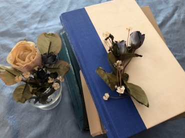 A stack of hardcover books on a blue cloth, with a dried white rose in a glass dish and some rose buds and leaves on the top book
