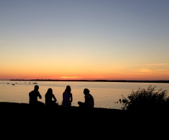 Sunset over water, with the silhouettes of four young people in the foreground
