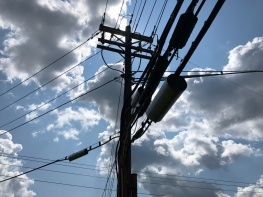A view of a power pole with many cables at many levels, silhouetted against a partly cloudy sky