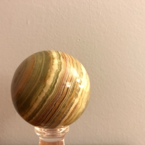 A polished sphere of agate showing bands of color in shades of green, tan, and red