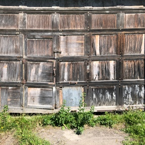 The door on this barn is made of weathered wooden squares with distinct vertical and horizontal grain