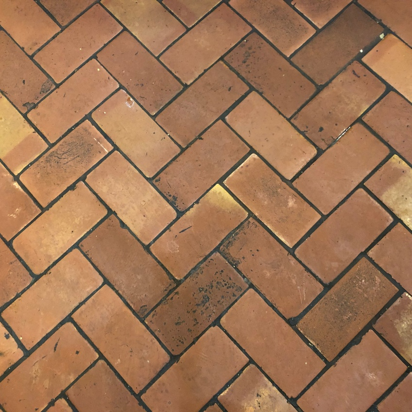 Red-orange bricks arranged in a herringbone pattern