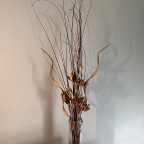 A vase holds an arangement of dried plant items, including tall thin twigs, spiral curled branches, and flower-shaped seed pods