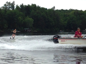 A boat pulling a water skier on a lake surrounded by dense trees. The skier is in the background, well up on her skis; the boater, in the foreground, is looking back, concentrating on keeping her safe.