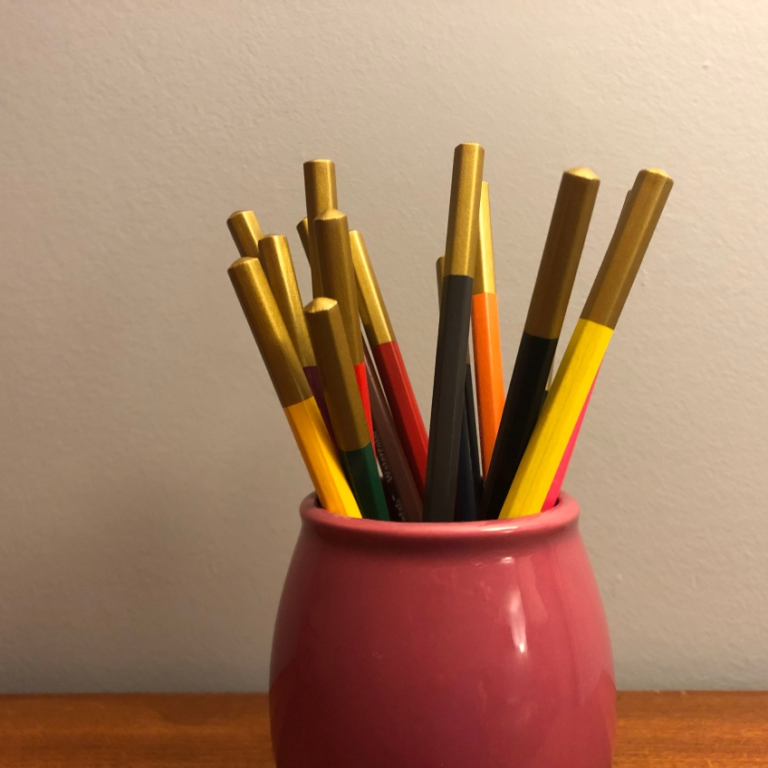 A pink cup holds an assortment of colored pencils with golden ends