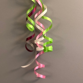 A tangle of spiral ribbons in pink, white, and green