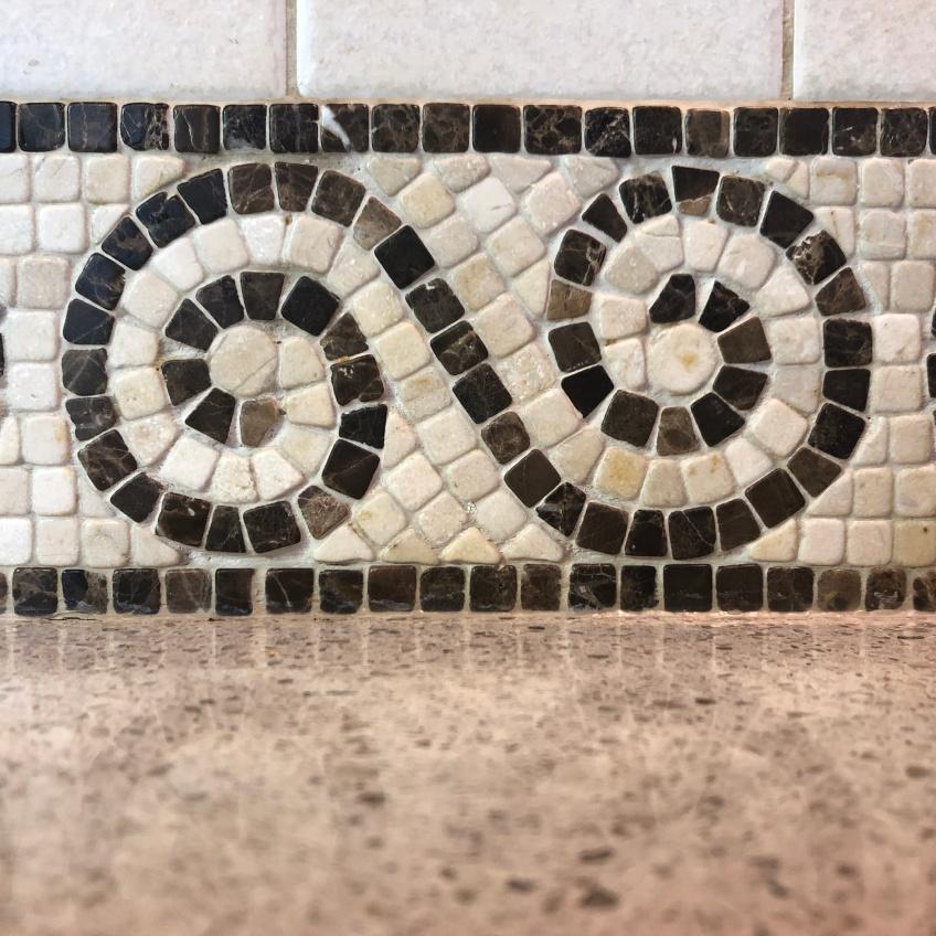 A mosaic tile backsplash has a spiral pattern between horizontal lines