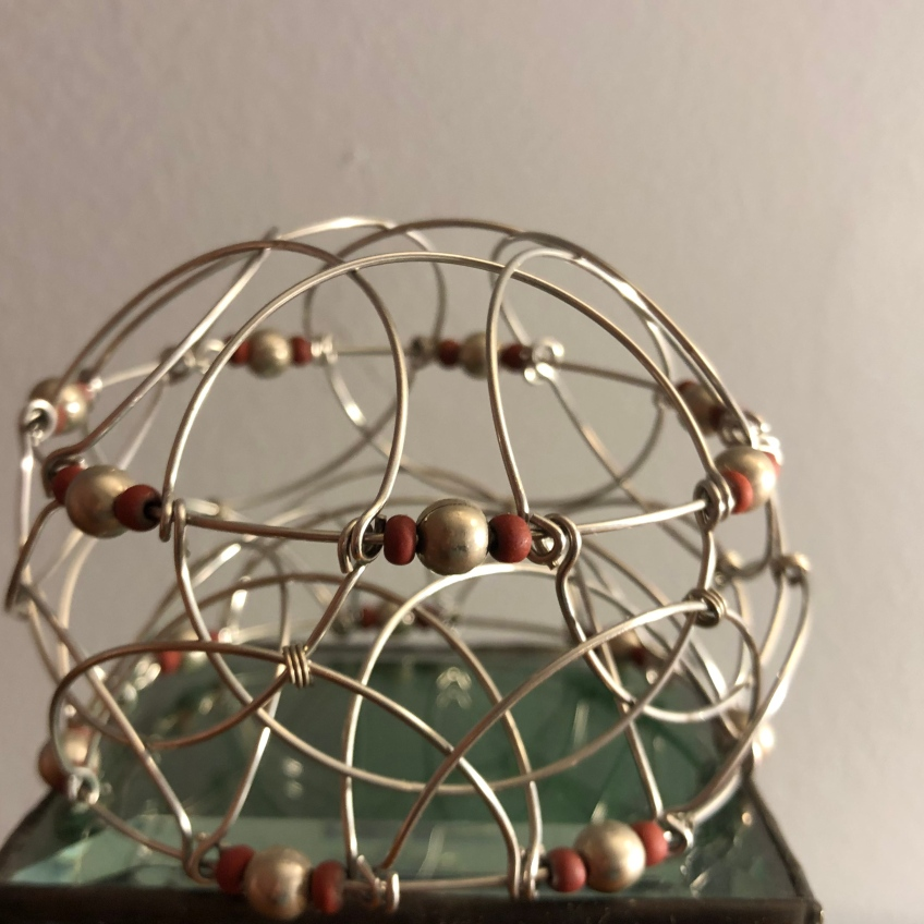 A flexible toy made of wire circles and beads