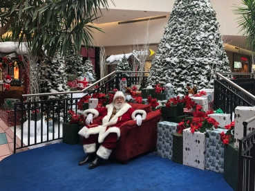 A mall Santa sits on his throne, surrounded by Christmas decorations, but with no children present
