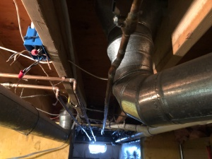Metal heating ducts, copper water pipes, and electrical wiring fastened to the ceiling joists